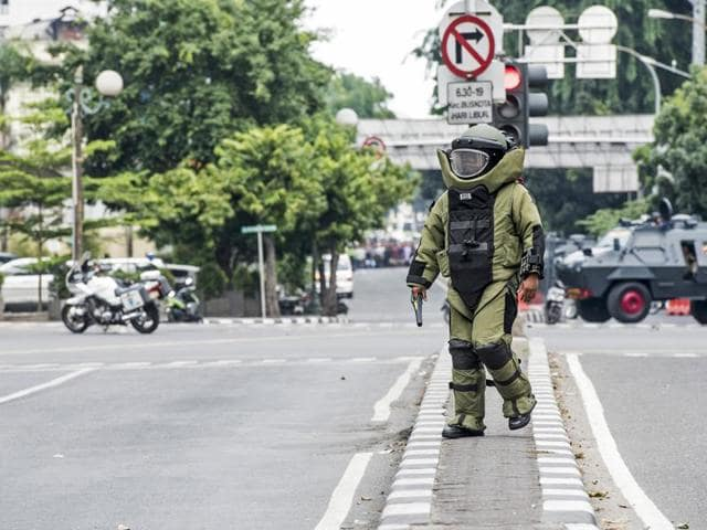 A member of the police bomb squad unit approaches the scene of an explosion following an attack on a police box in central Jakarta.