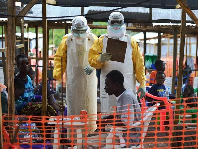 A MSF medical worker, wearing protective clothing relays patient details and updates behind a barrier to a colleague at an MSF facility in Kailahun. The World Health Organization (WHO) announced that the Ebola epidemic was over after Liberia, the last affected country, received the all-clear.