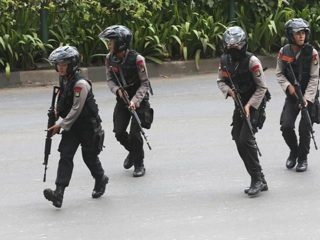 Police officers rush to take their position at the site of an attack in Jakarta. Attackers set off explosions at a Starbucks cafe in a bustling shopping area in Indonesia's capital and waged gunbattles with police.
