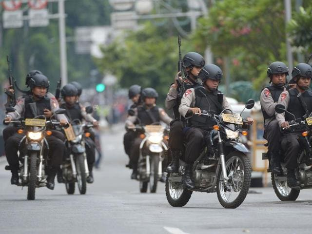 Indonesian policemen arrive to enter a building as armed men exchange shots with police in Jakarta.