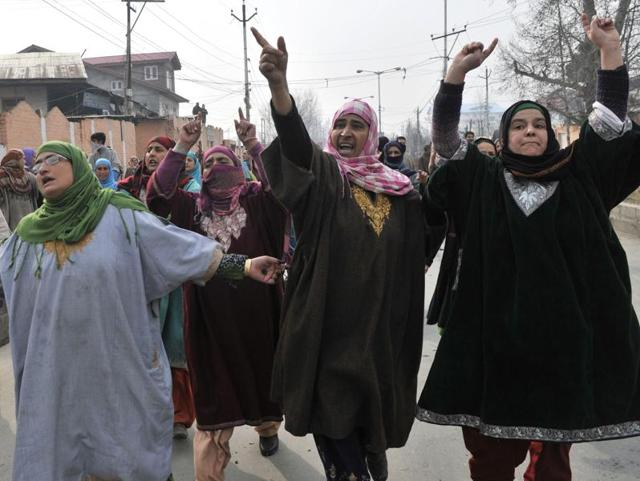 Kashmiri protesters throwing stones on policemen during protests in Srinagar, India, on Thursday.