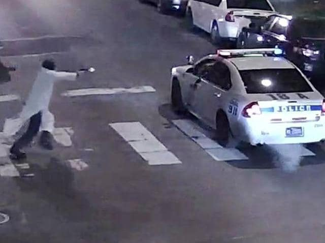 A still image from surveillance video shows a gunman (L) approaching a Philadelphia Police vehicle in which officer Jesse Hartnett was shot in Philadelphia.