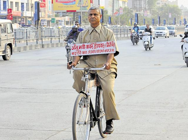 Suresh Tiwari uses a placard and roams the streets of Indore to advertise his driving services.