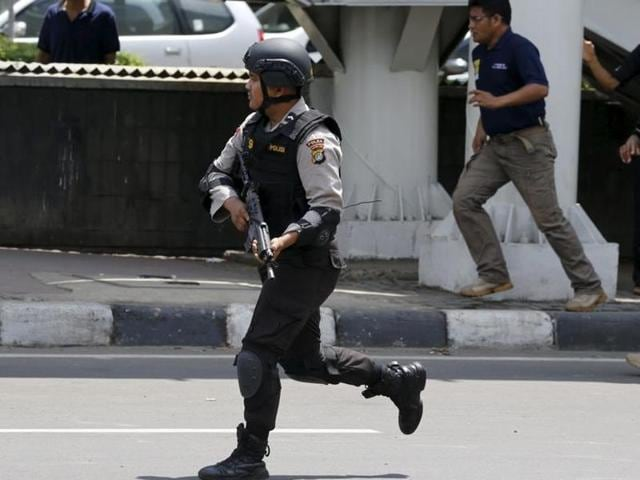 An Indonesian policeman runs near the site of a blast in Jakarta, Indonesia.