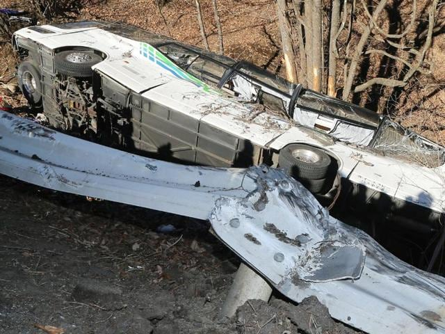 The wreckage of a bus which crashed after running off a road in Karuizawa, Nagano Prefecture, on January 15, 2016. Fourteen people were killed and dozens injured when a bus taking them to a ski resort ran off a mountain road in central Japan.
