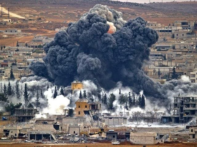 Smoke rises from the Syrian city of Kobani, following an airstrike by the US-led coalition against Islamic State. A US military report has stated that at least 8 civilians have been killed in the airstrikes, which have been aimed at IS targets.