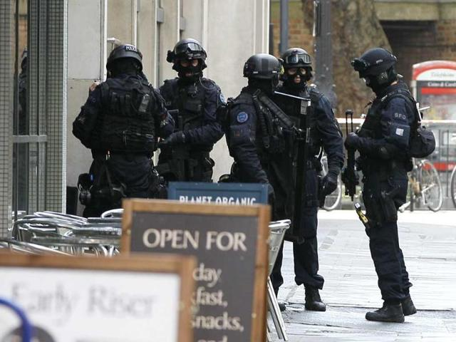 Armed police enter a building near Tottenham Court Road in London after a terror alert.