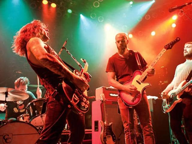 Baroness (left, with frontman and guitarist John Baizley in the centre) performs in Chicago in 2012.