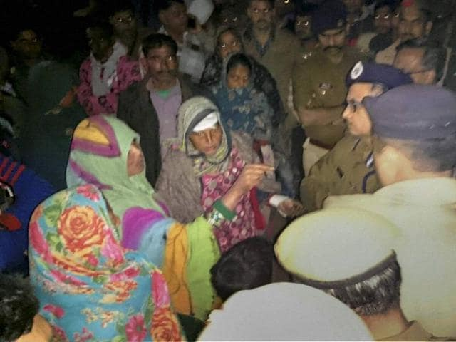 Police officers question local women after violent clashes erupted in Fatehpur.