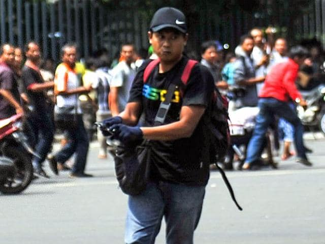 This picture taken on January 14, 2016 shows Afif carrying his weapon on the street during attacks in the Indonesian capital Jakarta.