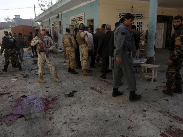 Afghan security forces inspect the site of a suicide attack in Jalalabad, Afghanistan.