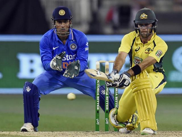 Australia's Glenn Maxwell hits a reverse sweep watched by India's MS Dhoni during their one day international cricket match in Melbourne.