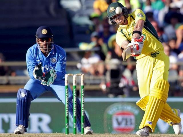 Australia's Steve Smith (R) hits a six as India's wicketkeeper MS Dhoni looks on during the One Day International cricket match in Perth January 12, 2016. The 3rd ODI will be played at Melbourne on January 17, 2016.