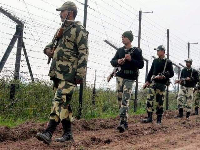 Border Security Force (BSF) soldiers patrol the border fence at Bamial border in Pathankot.