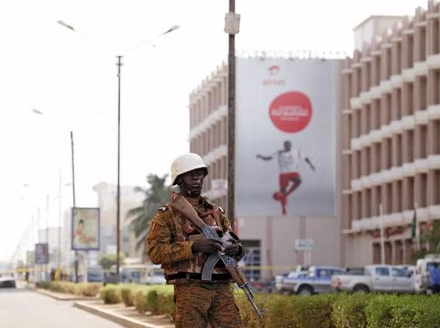 A soldier stands guard outside the Splendid Hotel in Ouagadougou, Burkina Faso on Saturday after security forces retook the hotel from al Qaeda extremists who seized it in an assault that killed over two dozen people .