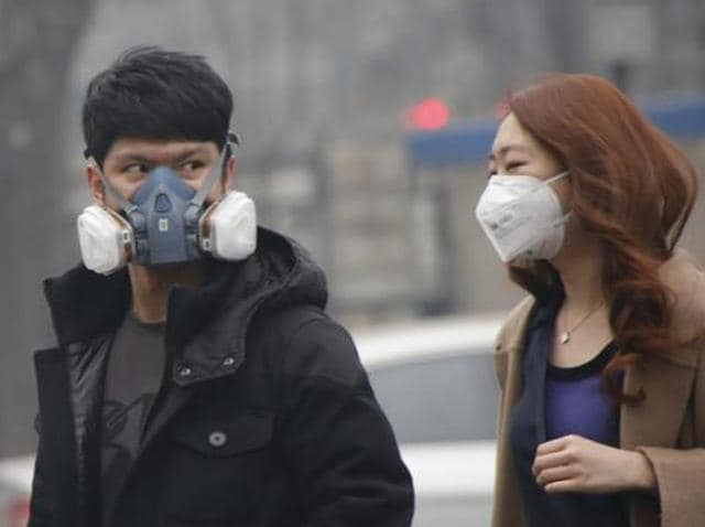 """A couple wearing masks make their ways in a shopping district in Beijing. World Health Organisation's top public health expert has termed air pollution a global """"public health emergency"""" that involves heavy costs on society."""