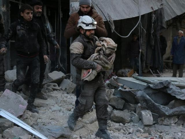 A Syrian Civil Defence worker carries a child wrapped in a blanket over the rubble following a reported air strike by Syrian government forces on the Sukkari neighborhood of Syria's northern city of Aleppo.