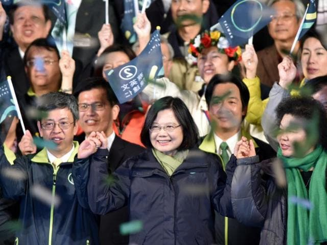 Taiwan's President-elect Tsai Ing-wen (C), from the Democratic Progressive Party (DPP), joins hands with counterpart Chen Chien-jen (L) after winning the elections in Taipei on January 15, 2016.