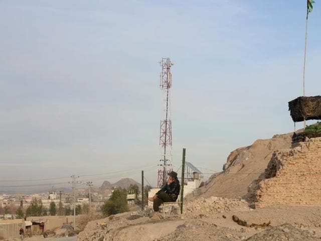 In this photograph taken on January 9, 2016, an Afghan policeman sits near a private cell phone antenna in Kandahar. The Taliban have demanded a hefty new