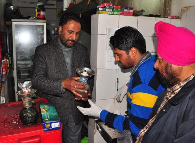 Crime branch officials collecting samples from a hookah bar at Sector 26 in Chandigarh on Sunday.