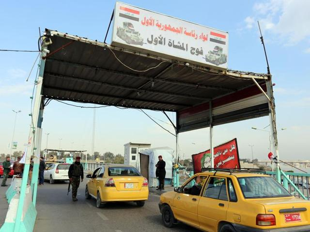 Iraqi security forces inspect a car at a checkpoint in Baghdad. US and Iraqi authorities were searching for three missing Americans said to have been kidnapped in southern Baghdad.