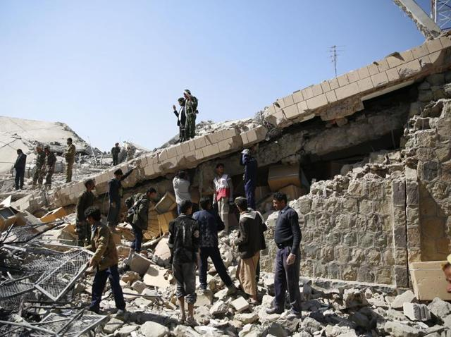 Policemen and people search for victims at the site of a Saudi-led airstrike on the police headquarters in Sanaa.