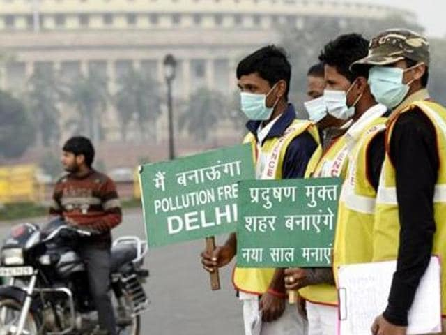 Civil defense personnel hold placards during the odd,even trial in front of the Parliament House, in New Delhi.