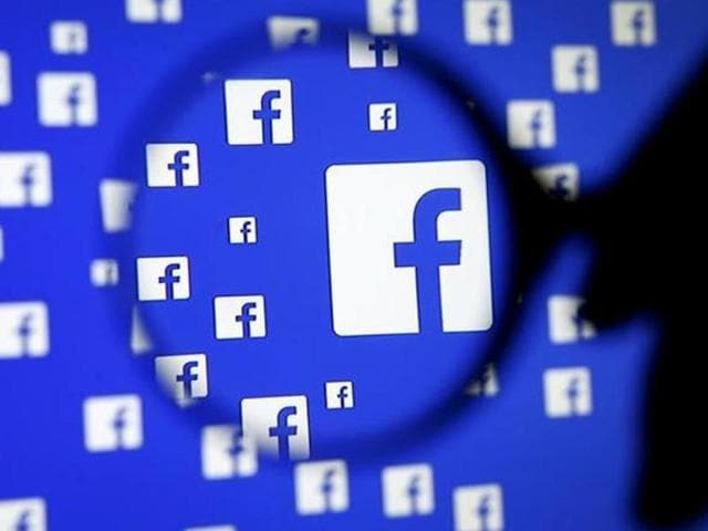 A man poses with a magnifier in front of a Facebook logo on display in this illustration taken in Sarajevo, Bosnia and Herzegovina.
