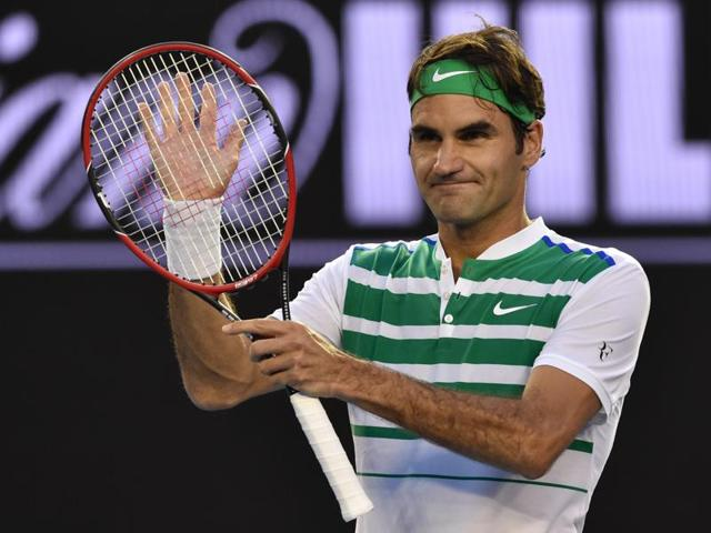 Switzerland's Roger Federer (R) shakes hands as he celebrates after victory in his men's singles match against Georgia's Nikoloz Basilashvili on day one of the 2016 Australian Open tennis tournament in Melbourne on January 18, 2016.