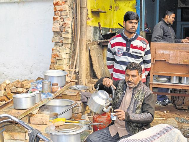 Vishnu Agarwal pours tea at his roadside stall in New Agra while his son Manoj looks on.