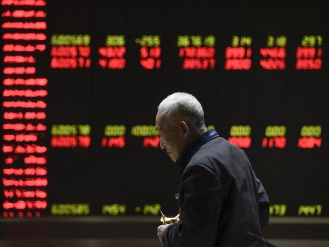 Investors are seen in front of an electronic board showing stock information at a brokerage house in Beijing. China's rate of growth has fallen to its worst since 2009.