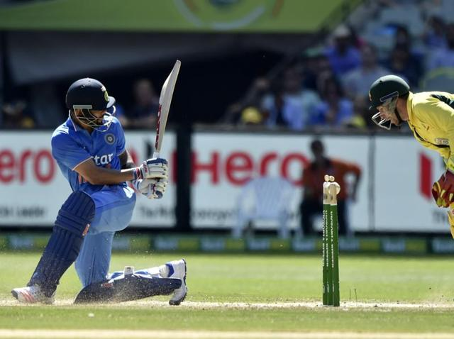 Australia's batsman Glenn Maxwell plays a shot as India's wicketkeeper MS Dhoni looks on during the third one-day international cricket match.