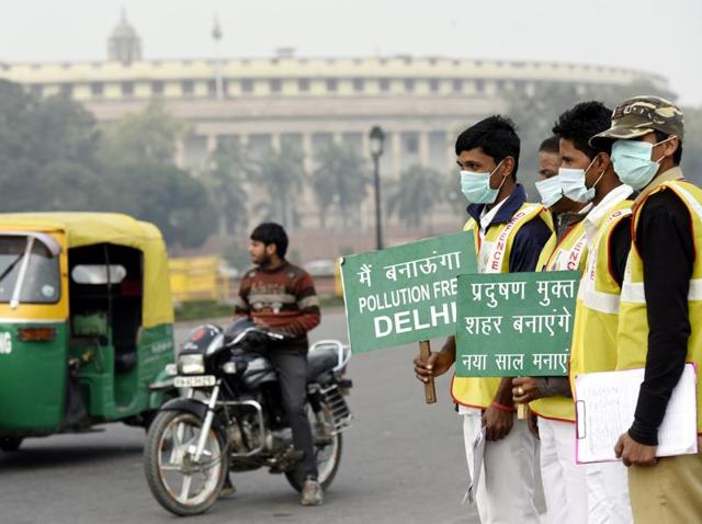 Civil defence personnel hold placards during the odd-even vehicular plan in front of the Parliament House, in New Delhi.