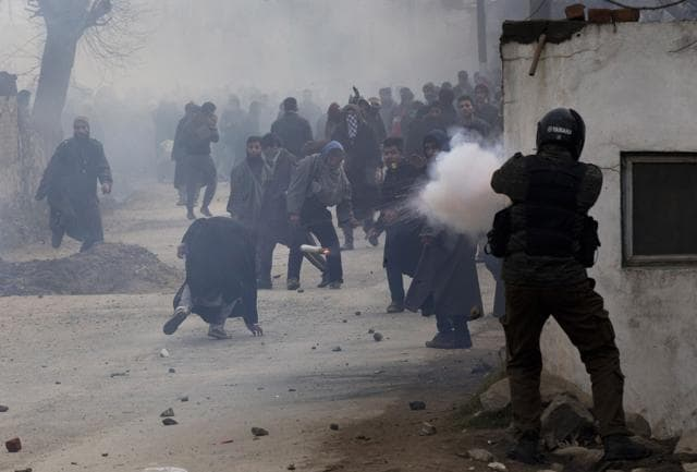 A police officer fires a teargas shell as a protester, (C) ducks to avoid it during the funeral procession for a separatist leader on the outskirts of Srinagar.