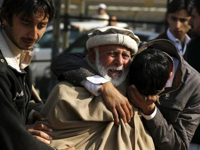 Relatives grieve their loss at the Hayatabad medical complex after a suicide bomber targeted a police checkpoint in Peshawar.