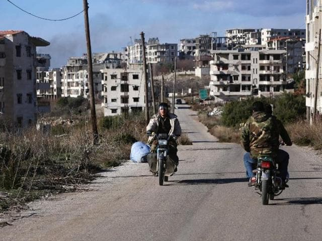Syrian pro-government forces drive motorbikes in the strategic town of Salma, in the coastal Latakia province, on January 15, 2016, following its recapture from rebel fighters.