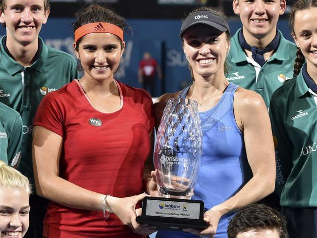 Sania Mirza and teammate Martina Hingis pose with the winning trophy after defeating Germany's Angelique Kerber and Andrea Petkovic in their women's doubles match.