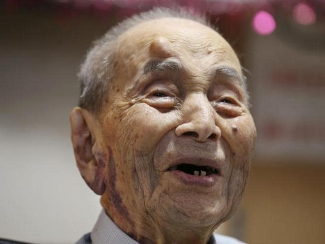 In this Aug. 21, 2015, file photo, Yasutaro Koide, 112, holds the Guinness World Records certificate as he is formally recognized as the world's oldest man at a nursing home in Nagoya, central Japan. Koide, who was born on March 13, 1903, has died on Tuesday.