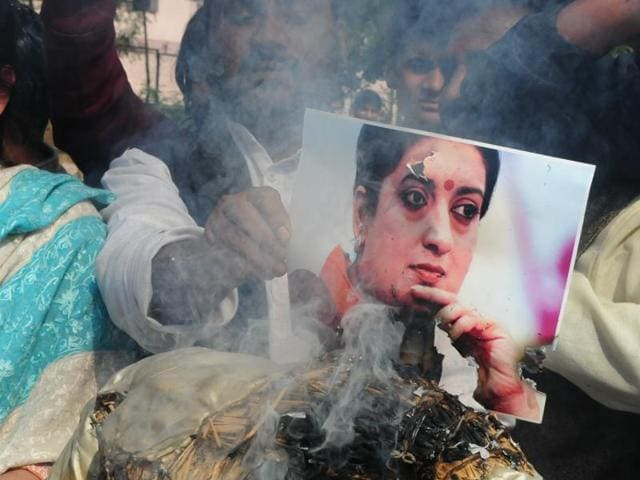 Congress workers burn HRD minister Smriti Irani's photograph during a protest in Bhopal on Wednesday.