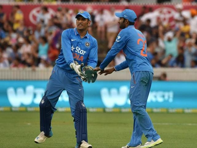 Indian captain MS Dhoni (L) congratulates Gurkeerat Mann (R) on successfully taking a catch.