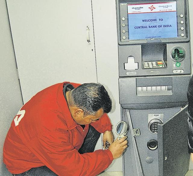 Fingerprint experts examining the Central Bank Of India ATM in Jalandhar on Wednesday.