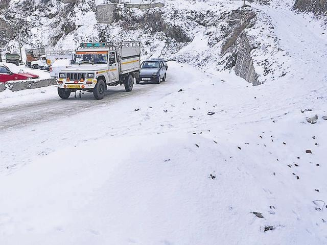 Vehicles proceed with caution as snow covers the  Sanjauli-Dhalli bypass in Shimla on Wednesday.