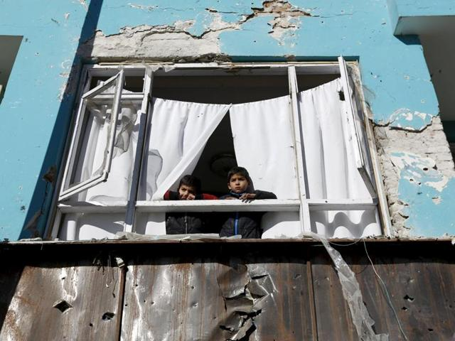 Afghan boys look out a window damaged after a last night suicide car bomb attack in Kabul, Afghanistan January 21, 2016. A Taliban suicide car bomber targeted a minibus carrying journalists working for a private Afghan television channel on Wednesday, killing seven employees, officials said.