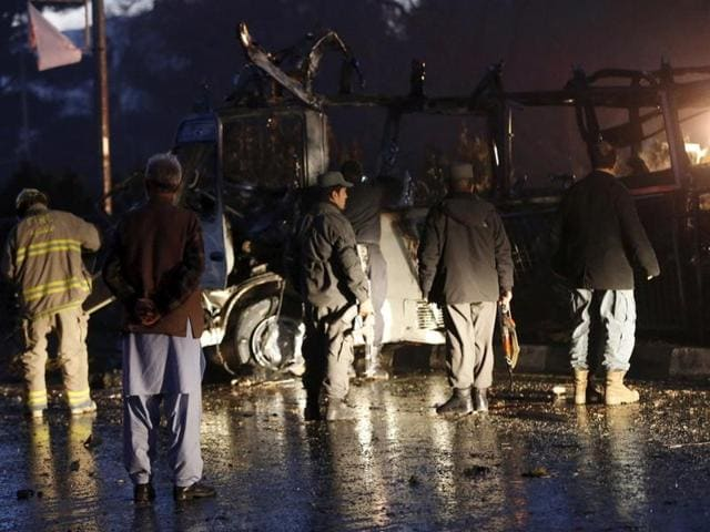 Afghan policemen and fire fighters inspect the wreckage of a bus that was hit by a suicide bomb attack, in an area near the Russian embassy in Kabul, Afghanistan.
