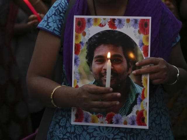 Activist of a Dalit organisation participate in a candle light vigil holding photographs of Indian student Rohith Vemula in Hyderabad.
