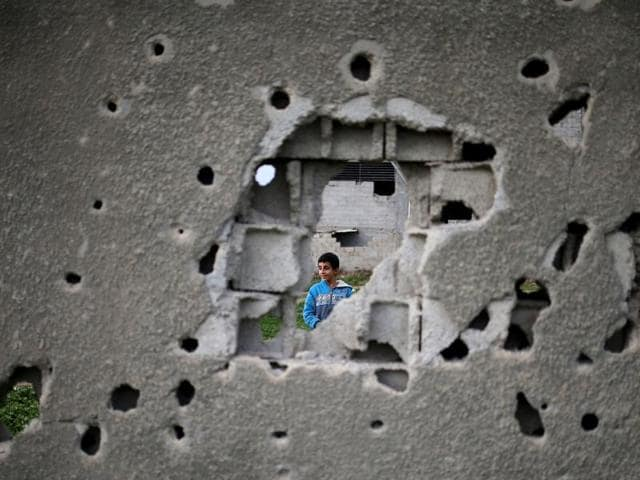 A Palestinian boy is seen through a bullet-riddled wall from a building which was destroyed during the 50-day war between Israel and Hamas in 2014, Gaza City.