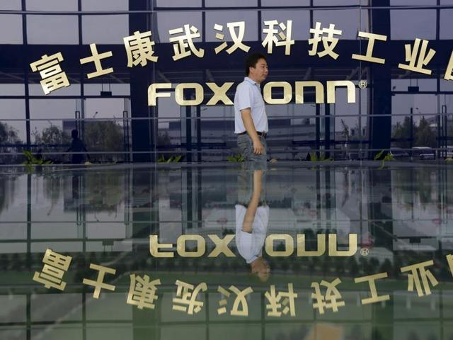 A man walks past a logo of a Foxconn factory in Wuhan, Hubei province, in this August 31, 2012 file photo.