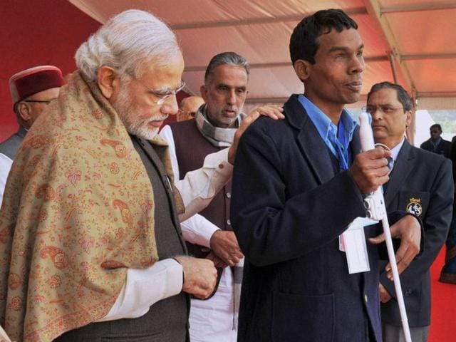 Prime Minister Narendra Modi interacting with a 'Divyang' (physically challenged) child while distributing aid & assistive devices at a function, in Varanasi on Friday.