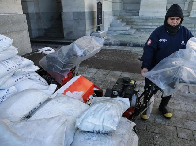 Surrounded by bags of ice-melting salt, stone mason Medaro Romero covers gas powered snow sweepers in plastic bags in preparation for a coming winter storm outside the U.S. Capitol January 21, 2016 in Washington, DC.
