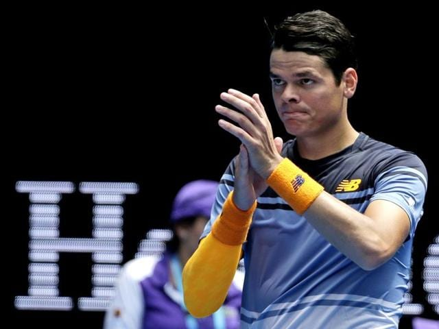 Canada's Milos Raonic (L) consoles Serbia's Viktor Troicki after Raonic won their third round match at the Australian Open in Melbourne on January 23, 2016.